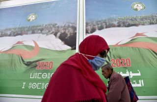 People walk past campaign billboards ahead of the upcoming constitutional referendum on a street in Algiers, Algeria, on Oct. 22, 2020.