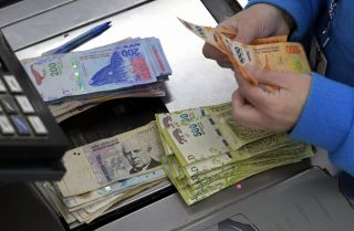 A supermarket cashier counts Argentine pesos in Buenos Aires on Aug. 15, 2019.