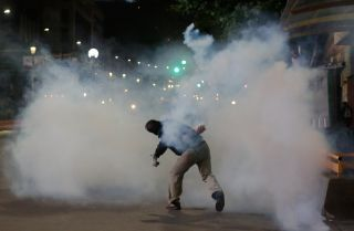 A demonstrator throws a tear gas canister during a demonstration against Bolivian President Evo Morales on Nov. 5, 2019, in La Paz, Bolivia.