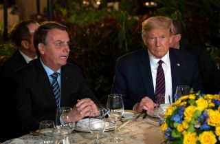 U.S. President Donald Trump (right) speaks with Brazilian President Jair Bolsonaro during a dinner at Mar-a-Lago in Palm Beach, Florida, on March 7, 2020.
