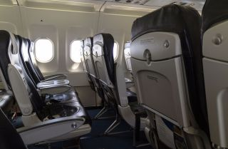 This photo shows a rows of seats on a passenger aircraft.