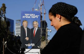 """An election billboard in Tel Aviv on Feb. 3, 2019, shows Israeli Prime Minister Benjamin Netanyahu and U.S. President Donald Trump shaking hands. The Hebrew writing reads, """"Netanyahu, in another league."""""""