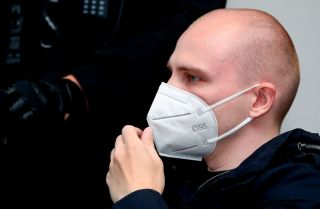 Stephan Balliet, who is accused of shooting two people dead after an attempt to storm a synagogue in Halle an der Saale, eastern Germany, wears a face mask as he waits for the start of the 18th day of his trial on Nov. 3, 2020, at the district court in Magdeburg, eastern Germany.