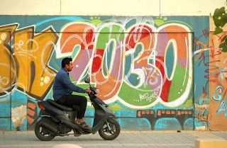 This photo shows a scooter rider passing graffiti alluding to the Saudi Vision 2030 modernization program