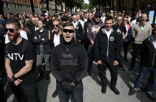 Supporters of the neo-Nazi Nordic Resistance Movement chant slogans during a demonstration in Stockholm, Sweden on Aug. 25, 2018.