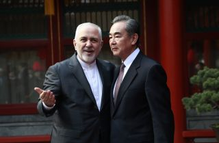 Iran's Foreign Minister Javad Zarif (L) gestures as he speaks with his Chinese counterpart, Wang Yi, during a meeting in Beijing on Feb. 19, 2019.