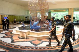 In this picture taken on May 1, 2019, Sri Lankan soldiers walk through the Cinnamon Grand Hotel lobby in Colombo. On April 21, the Cinnamon was one of three hotels hit by jihadi bombers along with three churches in attacks claimed by the Islamic State.