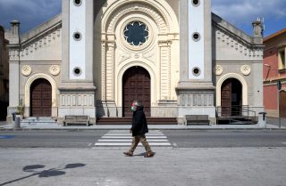 A man wearing a protective mask walks in the empty square in front of a cathedral in Locri, Italy, on April 7, 2020.