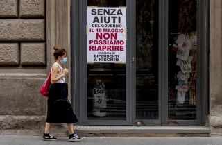 "A woman wearing a face mask walks past a closed shop in Rome, Italy, on May 18, 2020. The sign on the store window reads ""Without government aid, we cannot reopen on May 18. Thousands of employees at risk."""