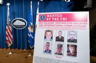 A poster showing six Russian intelligence officers charged with carrying out global cyberattacks is displayed before a news conference at the U.S. Department of Justice on Oct. 19, 2020, in Washington D.C.