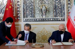 Iran and China's foreign ministers (right to left) sign a partnership agreement in Tehran on March 27, 2021.