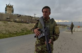 An Afghan soldier stands guard at a checkpoint outside a U.S. military base in Bagram, located roughly 50 kilometers north of Kabul, on April 29, 2021.