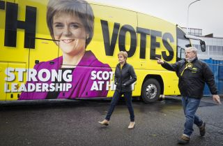 Scottish National Party (SNP) leader Nicola Sturgeon walks past her campaign bus with SNP candidate Angus Robertson in Edinburgh on May 4, 2021.