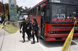 Police inspect one of four buses attacked by alleged gang members July 13, 2018, in Guatemala City.