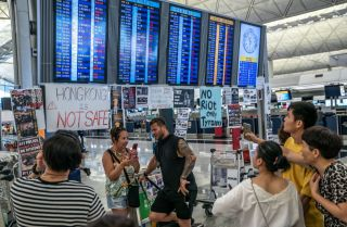 Tourists look at the information panel that shows all flights are canceled at Hong Kong International Airport during a demonstration on Aug. 12, 2019, in Hong Kong.
