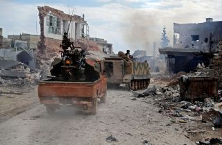 Members of the Syrian National Army, an alliance of rebel groups backed by Turkey, ride in the town of Sarmin, about 8 kilometers (5 miles) southeast of the city of Idlib in northwestern Syria, on Feb. 24, 2020.