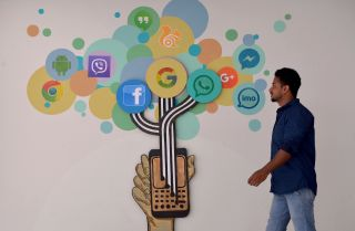 An Indian visitor walks past a mural of social media logos in Bangalore.