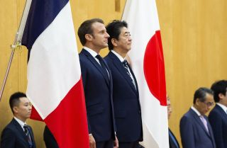 Japanese Prime Minister Shinzo Abe and French President Emmanuel Macron attend an official ceremony in Tokyo on June 26, 2019.