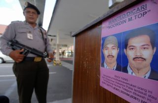 A policeman next to a poster of Noordin Mohammed Top on Aug. 8, 2009, at Bali's Denpasar airport.