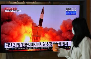 A woman walks past a screen showing footage of a North Korean missile test in Seoul, South Korea, on March 29, 2020.