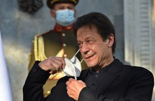 Pakistani Prime Minister Imran Khan removes his facemask during a press conference on Nov. 19, 2020.