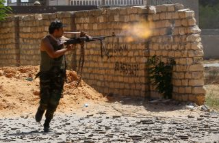 A fighter loyal to Libya's internationally recognized government in Tripoli fires on forces allied with Khalifa Hifter's Libyan National Army during clashes in Ain Zara on Sept. 7, 2019.