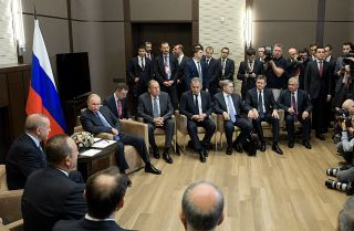 Turkish President Recep Tayyip Erdogan (L) and Russian President Vladimir Putin (in front of flag) sit during a meeting in Sochi to discuss the situation in Syria.