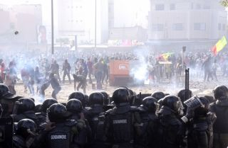 Protesters fight gendarmes on March 5, 2021, near their barracks in the Colobane neighborhood in Dakar, Senegal, during clashes following the arrest of the main opposition leader, Ousmane Sonko.