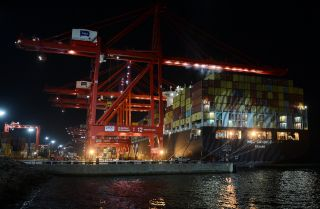 Workers at the Chinese-majority owned Colombo International Container Terminal (CICT) in Colombo load a cargo ship in this photograph from June 24, 2016.