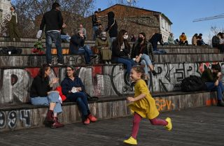 A child runs past people sitting near the Galata Bridge in Istanbul, Turkey, on Feb. 8, 2021.
