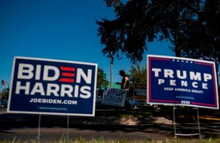 Biden and Trump campaign signs are displayed as voters line up to cast their ballots during early voting Oct. 30, 2020, at the Alafaya Branch Library in Orlando, Florida.