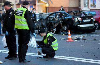 Two Ukrainian police officers investigate a car bombing in Kiev.