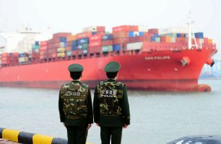 Chinese police officers watch a cargo ship in Qingdao, a seaport in Shandong province, on March 8, 2018.