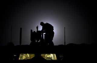 As the 10th anniversary of the Afghanistan War neared in 2011, a U.S. soldier readies his weapon at a forward operating base.