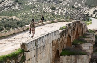 Turkish-backed Syrian opposition fighters walk on the Roman bridge in the archaeological site of Cyrrhus, northeast of the Syrian city of Afrin, in February 2018.