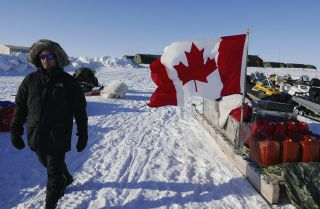 A project manager for the Arctic Research Foundation on April 9, 2015, walks past snowmobiles used by Canadian troops deployed to the territory of Nunavut to demonstrate Canadian sovereignty in the Arctic.