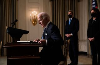 U.S. President Joe Biden prepares to sign executive orders after speaking about climate change issues in the State Dining Room of the White House on Jan. 27, 2021 in Washington D.C.  Behind him stands Special Presidential Envoy for Climate John Kerry (left) and Vice President Kamala Harris (right).