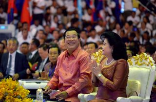 Cambodian Prime Minister Hun Sen (L) and his wife look on during a ceremony at the Olympic national stadium in Phnom Penh on July 17, 2017.