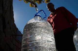 A man fills a plastic jug with drinking water from a spring-fed tap in Cape Town, South Africa. Prolonged drought conditions have put the city in danger of running out of water.