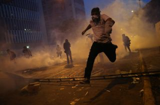 Protesters run from tear gas during an anti-government demonstration on during February in Caracas, Venezuela. A confrontation between government elites and a dissident faction of the ruling party is threatening to balloon into a wider conflict.