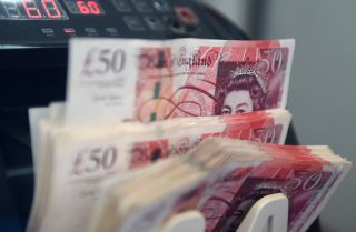 A counting machine tallies British pound notes Jan. 16, 2017, at a currency exchange in Kuala Lumpur, Malaysia.