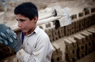 An Afghan child carries shovels at a brick factory in Kabul. The percentage of the world's population in slavery may be at its lowest point in history, but in absolute terms, the global number of enslaved people is higher than it's ever been.