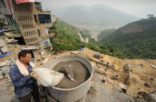 A worker in Badong, China, mixes cement.