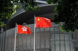 Flags of China (C) and Hong Kong (L) on March 30, 2021, outside the Legislative Council complex in Hong Kong.