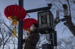 A worker hangs traditional red lanterns for the upcoming Spring Festival on Feb. 3, 2021, in Beijing.
