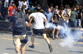 This picture shows a Chinese demonstrator throwing back a tear gas bottle during an anti-Japan protest in September 2012.