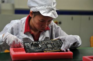 A worker inspects motherboards on a factory line at the Foxconn plant in Shenzhen, China, in 2010.
