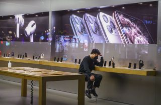 An employee sits in the showroom of an Apple store in Beijing after it closed for the day on Feb. 1, 2020.