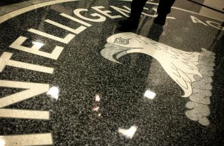 A man walks across the seal of the Central Intelligence Agency at the lobby of the Original Headquarters Building at the CIA headquarters.