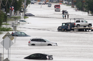 Cars and trucks sit swamped in floodwaters in Houston.